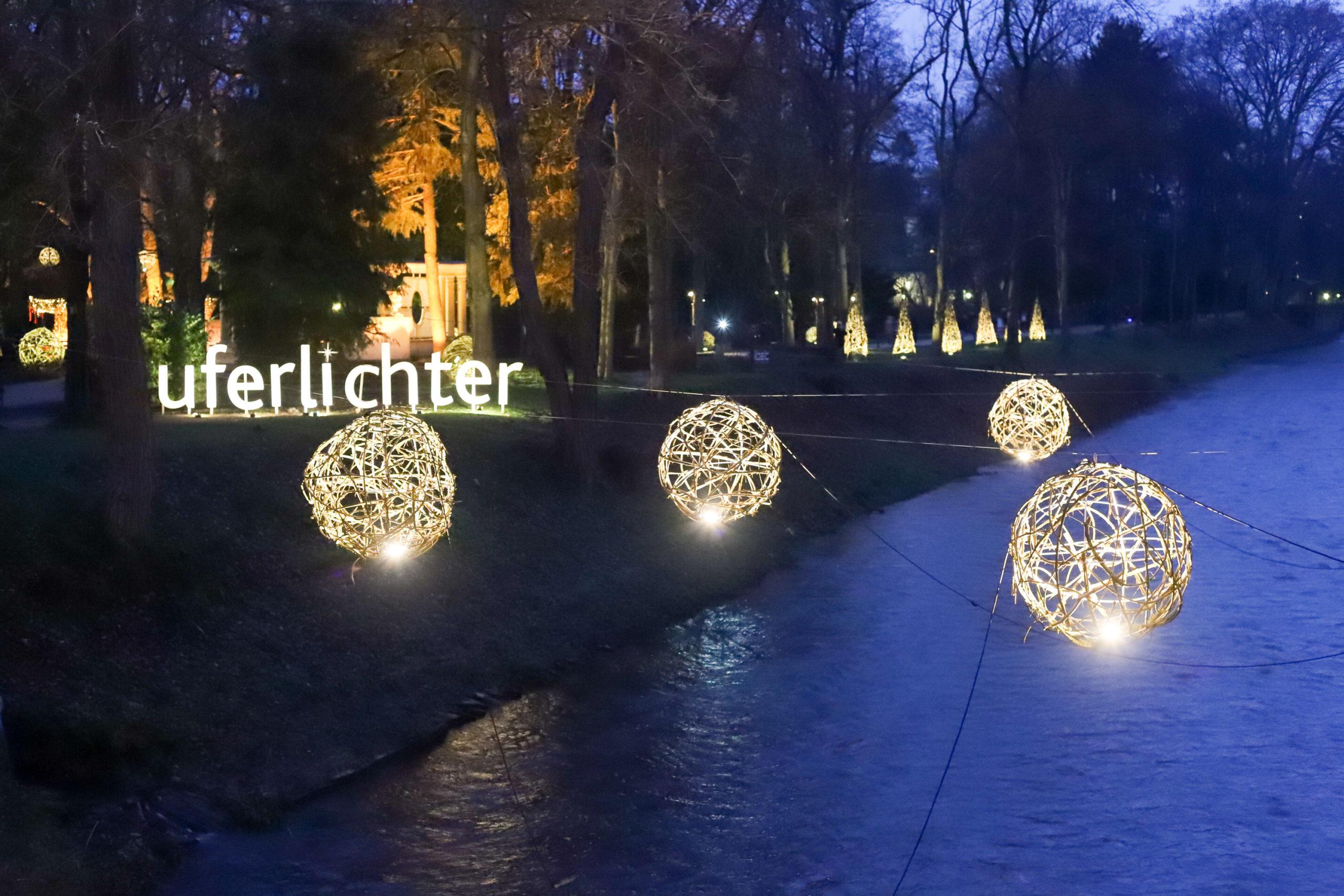 """Von der Brücke ans linke Ufer fotografiert. Über dem Wasser hängen vier mittelgroße Kugeln aus Holz geflechtet und beleuchtet. Am Ufer steht ein Leuchtschriftzug """"Uferlichter"""". Im Hintergrund sind beleuchtete Dreiecke, die an Weihnachtsbäume erinnern, zu erkennen."""