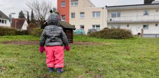 Kind von hinten, das auf ein kleines Holzhaus auf dem Spielplatz blickt, auf dessen Dach zwei andere Kinder turnen.
