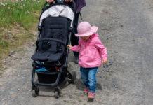 Das Kind in rosa Jacke und rosa Sonnenhut läuft – sich an ihm festhaltend – neben dem Buggy her.