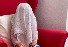 Das Kind sitzt in einem roten Sessel aufrecht und hat sich ein Tuch über den Kopf gezogen.