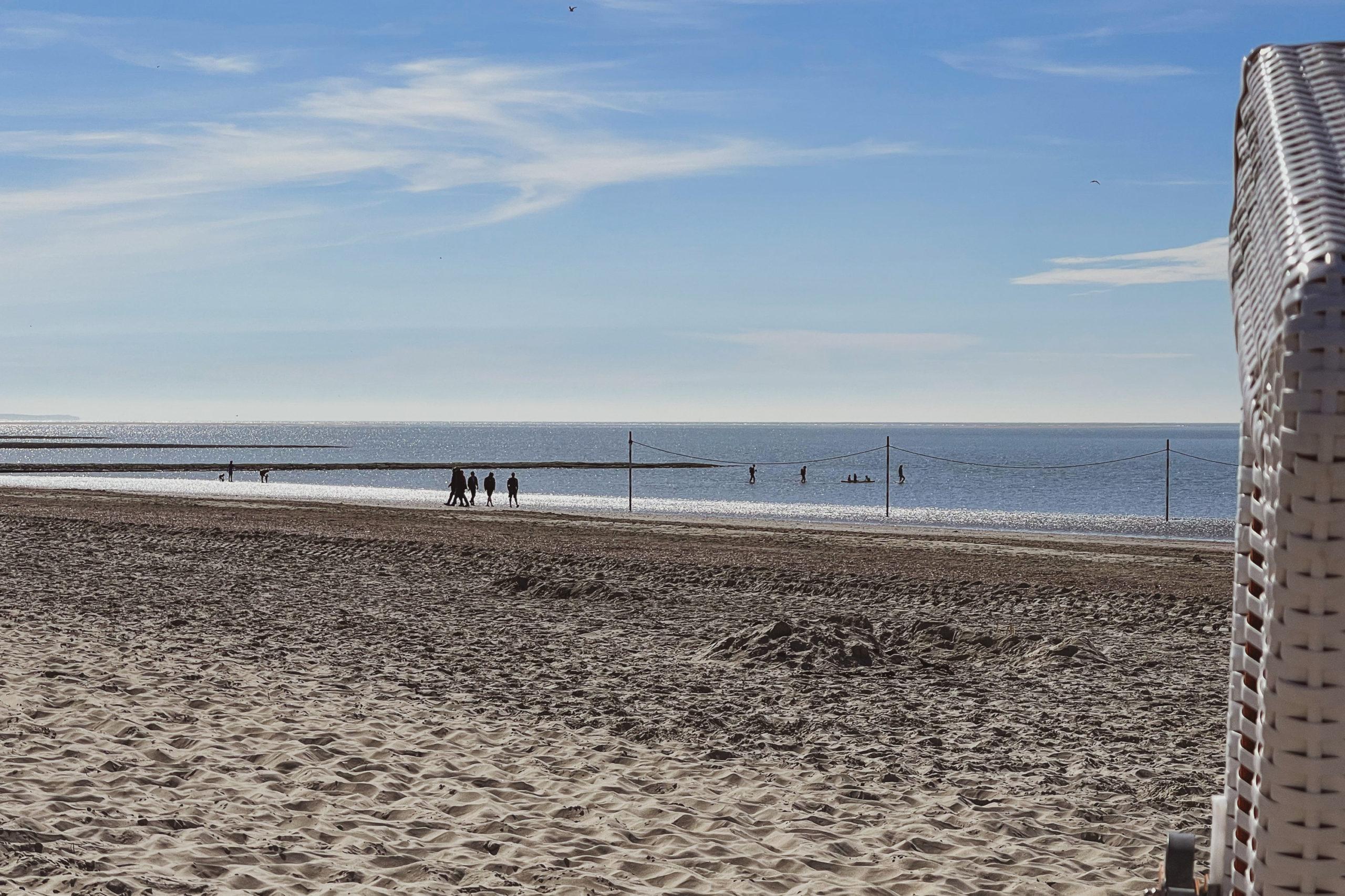 Blick am Strand zum Meer. Ein paar Menschen laufen am Wasser entlang. Am Bildrand rechts ist noch ein Standkorb zu erkennen.