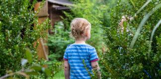 Ein kleines Kind im blau-hellblau geringelten Kleid von hinten. Es scheint jemandem zuzusehen.