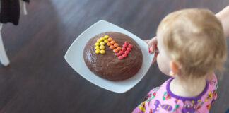 Das Kind von schräg oben hinten, es blickt auf einen Teller mit einem runden Schokokuchen, auf dem mit bunten Smarties eine 2 gelegt wurde.