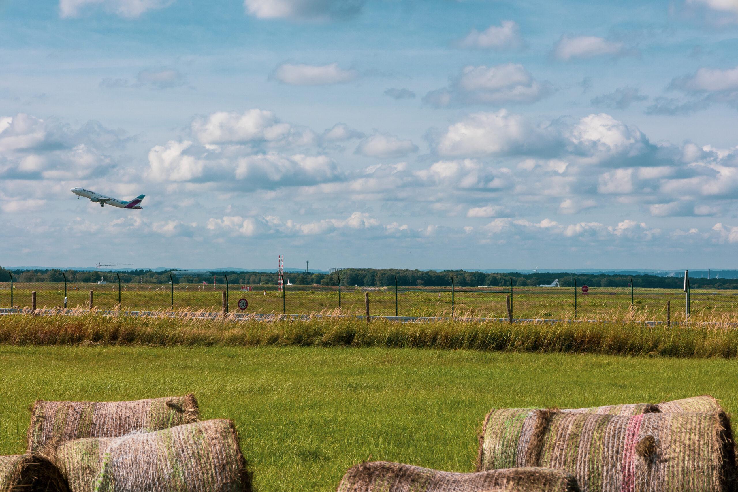 Flache Landschaft, im Vordergrund Heuballen, im Hintergrund startet gerade ein Flugzeug vom Flughafen.