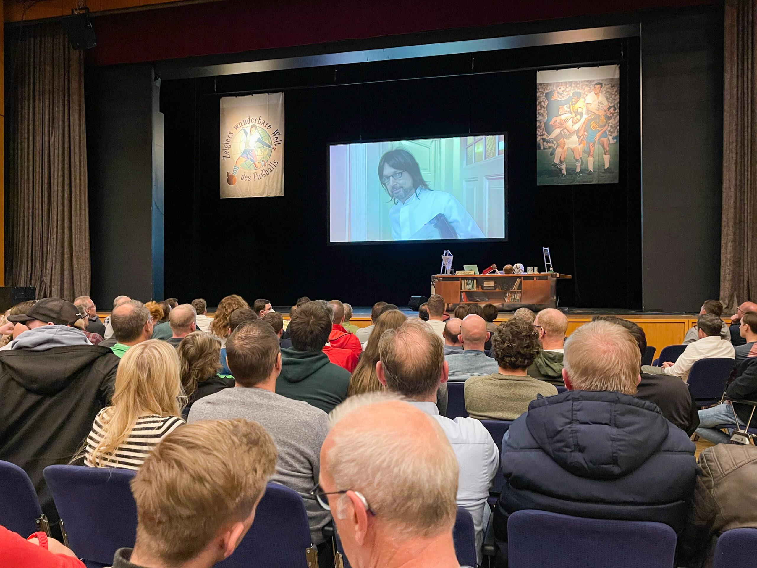 Menschen sitzen dich an dich vor einer Bühne, auf der ein Schreibtisch steht, dahinter eine große Leinwand, auf der ein Mann mit halblangen Haaren, Bart und Brille ins Publikum blickt.